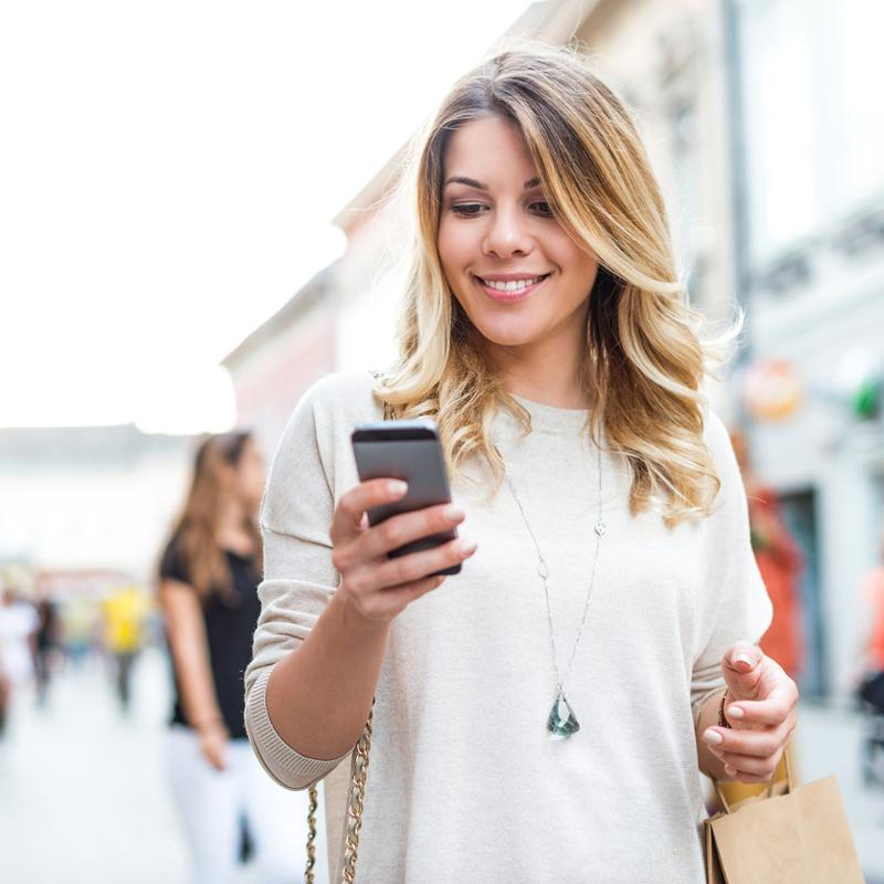 Woman using CAA Rewards app while shopping